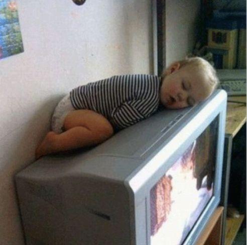 テレビの上で寝る子供